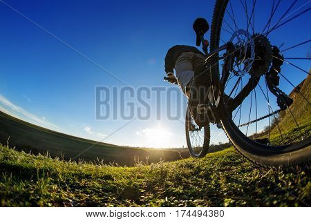 Riding a bike down a trail, close-up the rear wheel. Showing of the workings of the bike. Shallow depth of field. Detail of the cyclist. Green field and grass. Fisheye. Spring saeson in the countryside.