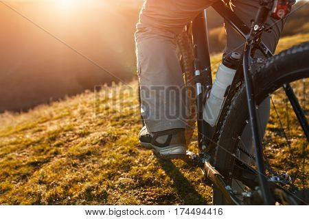 cyclist legs riding mountain bike on the hill in spring time. Close-up. Detail of the cycle. Whell and bottle. Legs and shoes. Field, grass and sun. Travel in the countryside.