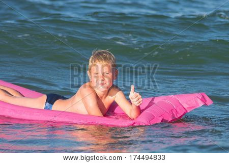Little kid swimming in the sea on inflatable mattress and shows ok. Smiling boy playing on the water. Summer vacation.