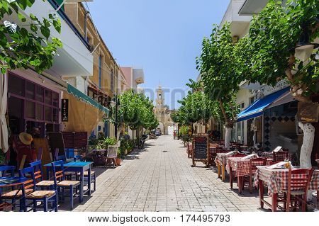 Paleochora, CRETE, GREECE - JUNE 2016: Street of Sitia town with shops and bars on Crete island, Greece