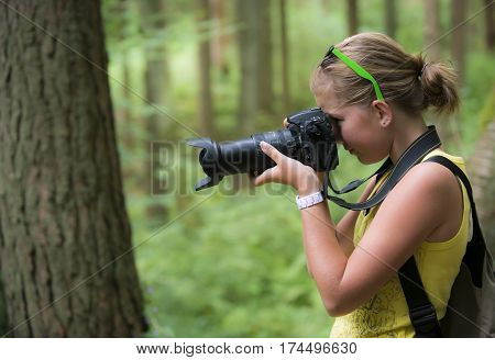 girl with a digital camera taking pictures outside