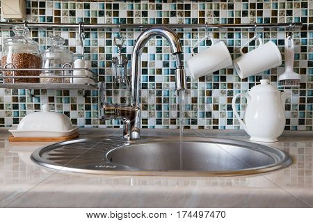The concept of wasteful use of water. Open kitchen faucet spouting water