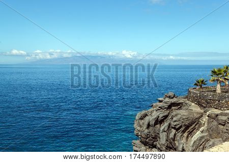 Island in the ocean and palms on the cliff. Island of La Gomera seen from the island of Tenerife on a sunny day. Canary Islands Spain