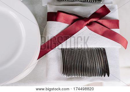 Wedding table decoration of the white napkin with the vinous ribon