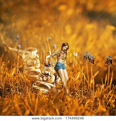 Creative surreal photomanipulation with a beautiful girl near the giant shoe and ladybug in the middle of a grass field with blue flowers at a sunny day of spring