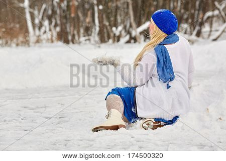 Plump smiling woman in skates sits in snowdrift and catches snowflakes on mitten at outdoor skating rink in winter park.