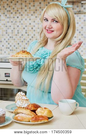 Plump smiling woman sits holding two plates with homemade baked sweets at table in kitchen.
