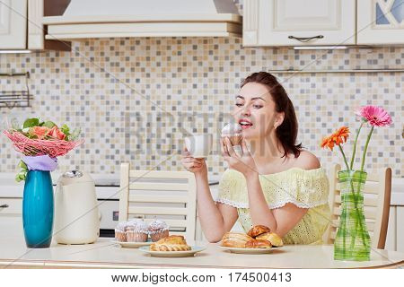 Young woman in yellow dress sits at table in kitchen, eats homemade cupcake and drink tea.