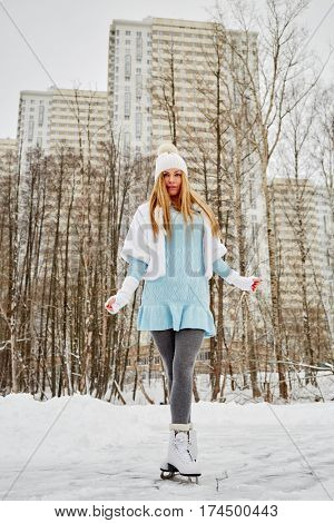 Young woman poses standing on skates at outdoor skate rink in winter park against highrise buildings.