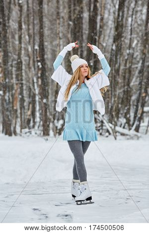 Young woman poses standing on skates at outdoor skate rink in winter park.