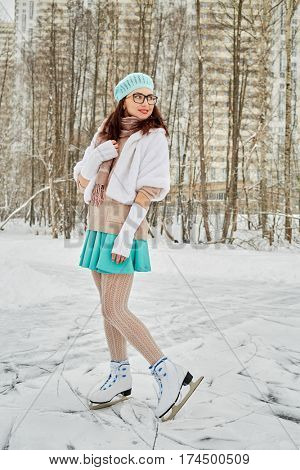 Young woman in glasses poses at outdoor skate rink in winter park against highrise buildings.