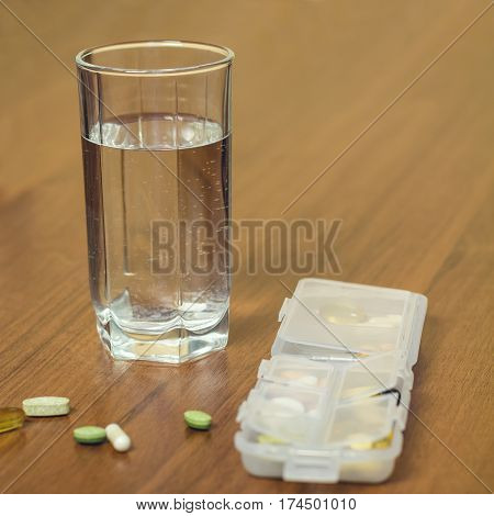 Glass of water and mixed natural food supplement vitamin pills in container on wooden table