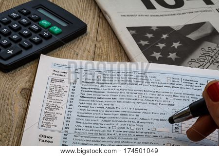 Tax preparation and review of US 1040 form with instructional booklet and calculator on wooden table