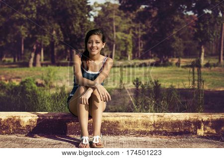 happy young woman in a sunny summer day in a park