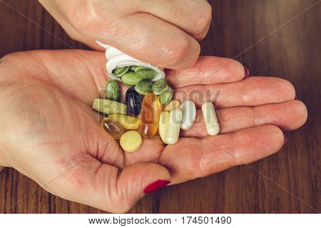 Woman's hands poured the mix of vitamins and nutritional dietary supplement pills from a bottle close-up