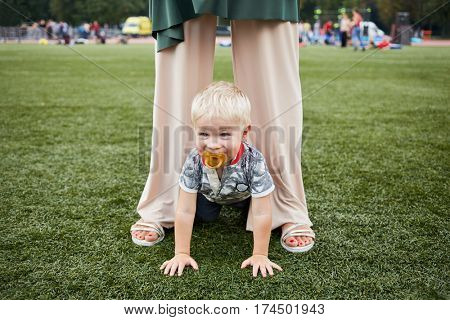 Little boy with dummy in mouth stands on fours between mother legs on green grass.