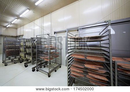 Wheeled racks with red fish fillet and smoked herring at factory work shop.