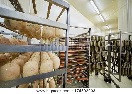 Racks with sausages, red fish and herring at factory.