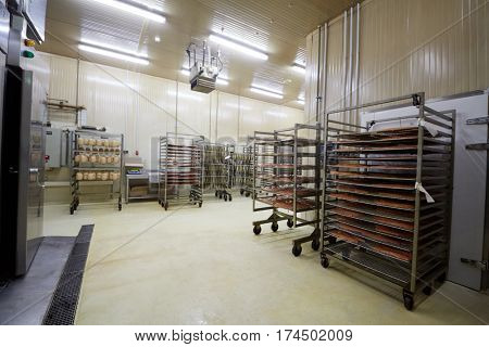 Wheeled racks with sausages, red fish fillet and herring at factory.