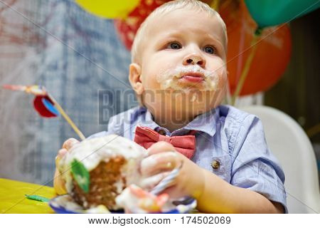 Little boy with smudged face eats birthday cake sitting at table.
