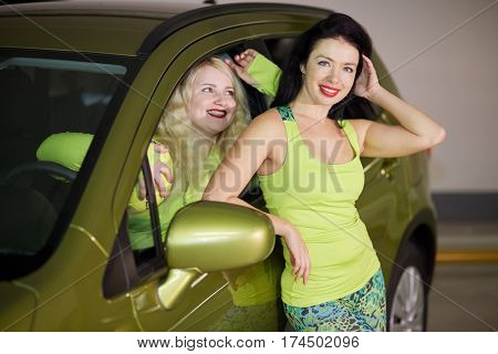 Two smiling girl at underground parking, one of them sits in car and another stands leaning her elbow on car window.