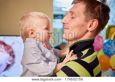 Happy father holds little son in arms.