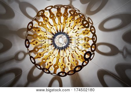 Modern burning chandelier at ceiling and shadows around, view from below.
