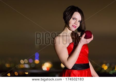 Half-length portrait of young woman in red dress stands at roof railing holding red apple in hand.