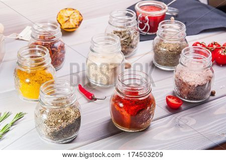 Close Up Assortment Of Colorful Spices In Glass Jars On The Wooden White Background. Selective Focus