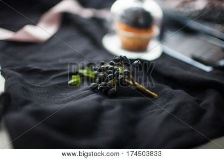 Boutonniere from a branch with black berries and green leaves on a black cloth. Wedding decorations