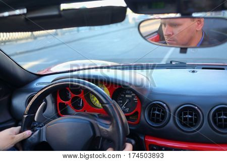 successful businessman behind wheel driving luxury roadster