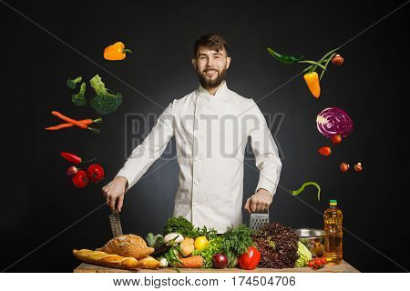 Chef cook in commercial kitchen. Professional chef stand on black background near the table with many frish healthy fruits and vegetables. Happy smiling chef preparing meal with various vegetables