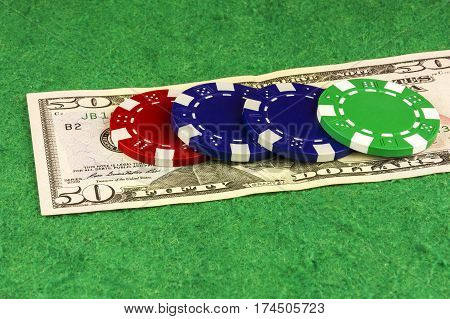 On the green baize is fifty dollars and casino chips