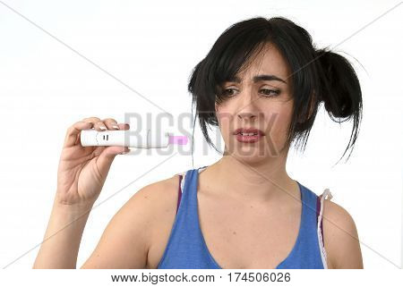 young pregnant woman scared in shock checking pink positive result on pregnancy test surprised and stressed in accidental motherhood and unwanted baby isolated on white background