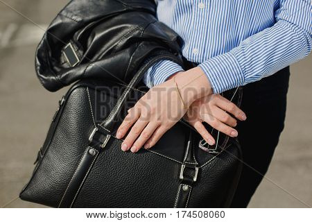 Business style clothing. fashion details, caucasian business woman holding black bag closeup.
