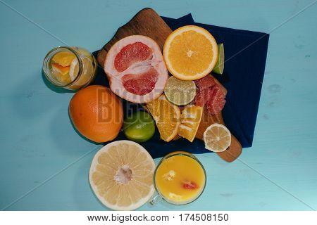 Citrus, oranges, lemons, limes, grapefruit, pomelo on vintage board lemonade on a turquoise background