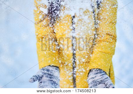 Girl in the yellow jacket throws snow in the air in cold weather. Cheerful winter mood in women