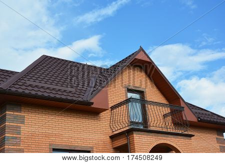 New roofing construction with attic balcony rain gutter system roof windows and roof protection from snow board snow guard house exterior.