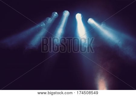 Several blue stage lights in the dark