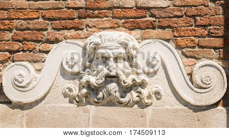 Detail of an ancient stone fountain depicting the god Neptune from whose mouth the water came out.
