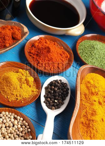 Colorful assortment of spices and herbs on a blue rustic wooden table