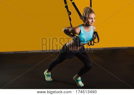 Sporty woman doing hand exercises with suspension straps at contemporary gym, copy space for text. Suspension training for slim body