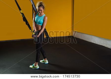 Sporty woman doing hand exercises with suspension straps at contemporary gym smiling and looking the camera. Suspension training for slim body