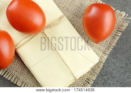 Three fresh red tomatoes and sheets for Italian lasagne on sackcloth and dark background.