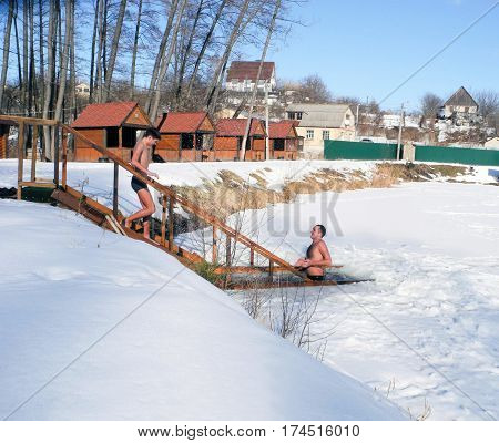 Man plunge into the winter ice-hole in lake after a sauna.