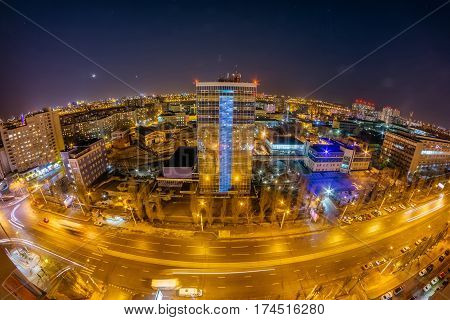 Night Voronezh cityscape from rooftop. Panorama of Leninskiy Prospect, glass business center