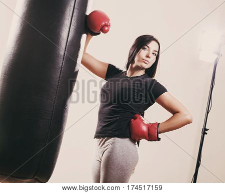 brunette boxing girl in boxing gloves and body hitting pear.