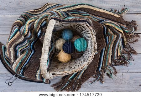 Knitted woolen scarf and yarn balls in a wicker basket on a wooden surface