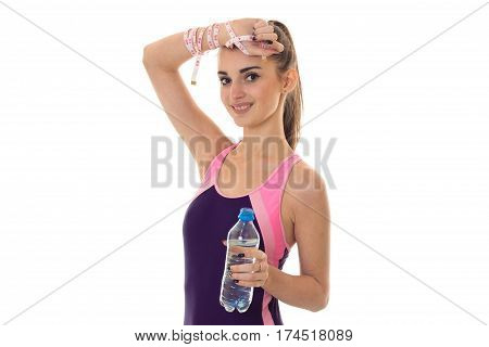 beautiful slender girl in a sports suit smiles kept her head and holding a bottle of water isolated on white background