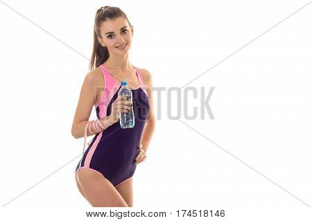 beautiful slender girl in a sports suit smiling keeps the water and looks into a camera isolated on white background